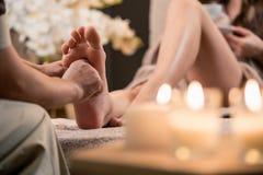 Vrouw die de massage van de reflexologyvoet in wellness spa hebben stock foto