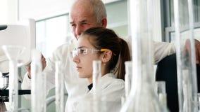 Vrouw die de microscoop voor medische test gebruiken stock video