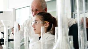 Vrouw die de microscoop voor medische test gebruiken stock footage