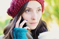 Vrouw die de mobiele telefoon uitnodigen en een kop van koffie houden stock foto