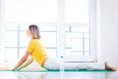 Vrouw die de oefening van de YOGA thuis doet Stock Foto