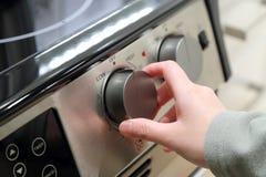 Vrouw die de oven aanzetten stock foto