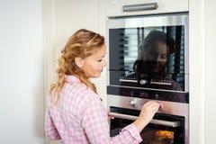 Vrouw die de oven in de keuken aanzetten royalty-vrije stock fotografie