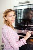 Vrouw die de oven in de keuken aanzetten royalty-vrije stock afbeelding