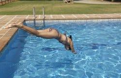 Vrouw die in de pool springen stock foto's