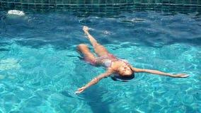 Vrouw die in de pool zwemmen die in langzame motie ontspannen 1920x1080 stock videobeelden