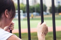 Vrouw die de poort houden bekijkend het gebied Stock Foto