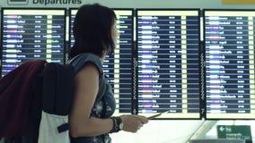Vrouw die de Raad van het Tijdschemavertrek bij luchthaven bekijken stock footage