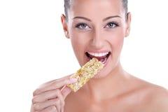 Vrouw die de snack van de mueslistaaf eet Stock Afbeelding