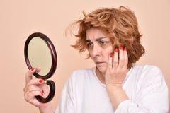 Vrouw die de spiegel bekijkt Stock Afbeeldingen
