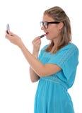 Vrouw die de spiegel bekijkt die lippenstift toepast Royalty-vrije Stock Afbeeldingen