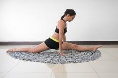 Vrouw die de spleet in yoga opwarmen Stock Fotografie