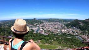Vrouw die de stad van Lourdes, beroemd voor zijn bedevaart kijken stock footage