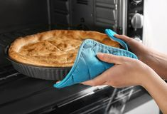 Vrouw die de uit gebakken pastei van de kippenpot van oven nemen, stock foto's