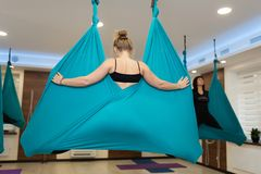 Vrouw die de uitrekkende oefeningen van de vliegyoga in hangmat doen Pasvorm en wellnesslevensstijl royalty-vrije stock afbeelding