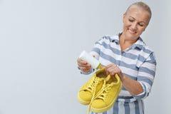 Vrouw die de verfrissing van de poederschoen in schoeisel op witte achtergrond zetten royalty-vrije stock afbeelding