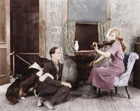 Vrouw die de viool voor haar vriend en hond spelen (Alle afgeschilderde personen leven niet langer en geen landgoed bestaat Lever royalty-vrije stock afbeelding