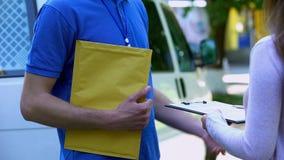 Vrouw die de vorm van de bewijslevering ondertekenen en geel pakket van koerier ontvangen stock afbeelding