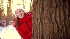 Vrouw die de winter van dag in openlucht genieten Het gelukkige meisje verbergen achter grote boom in de winterpark in langzame m stock video