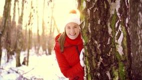 Vrouw die de winter van dag in openlucht genieten Het gelukkige meisje verbergen achter grote boom in de winterpark in langzame m stock footage