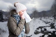 Vrouw die in de winterkleren een weefsel houden aan haar neus royalty-vrije stock foto