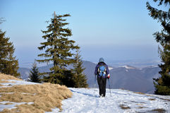 Vrouw die de wintertrekking in de bergen doen Stock Foto's