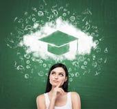 Vrouw die de wolk met graduatiehoed bekijken over het hoofd Groen schoolbord als achtergrond Stock Afbeeldingen