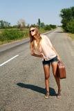 Vrouw die in de zomer met koffer op weg in platteland liften Stock Fotografie