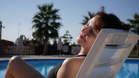 Vrouw die de zomer van dag genieten bij het hotel van de strandtoevlucht, wat betreft vlotte onthaarde benen Dame die door de poo stock video