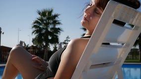 Vrouw die de zomer van dag genieten bij het hotel van de strandtoevlucht, wat betreft vlotte onthaarde benen Dame die door de poo stock footage