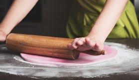 Vrouw die deegrol met behulp van die koninklijk suikerglazuur voor cake het verfraaien voorbereiden royalty-vrije stock foto's