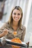 Vrouw die deegwaren eet bij koffie Royalty-vrije Stock Foto's