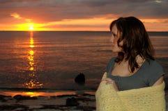 Vrouw in deken bij zonsondergang wordt verpakt die royalty-vrije stock afbeelding