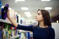 Vrouw die detergens in supermarkt kiest Royalty-vrije Stock Afbeeldingen