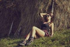 Vrouw die dichtbij een hooiberg rusten Royalty-vrije Stock Afbeeldingen