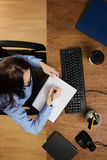 Vrouw die die bij bureau werken hierboven wordt geschoten van Stock Fotografie
