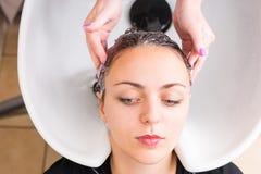 Vrouw die die Haar hebben door Stilist in Salon wordt gewassen stock foto's