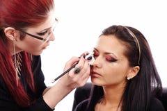 Vrouw die die make-up hebben door make-upkunstenaar wordt toegepast royalty-vrije stock afbeelding