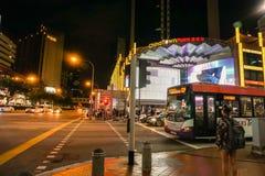 Vrouw die die op verkeersteken voor de kruising van weg wachten bij nacht wordt genomen Royalty-vrije Stock Fotografie