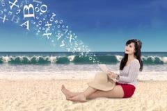 Vrouw die digitale tablet houden bij bach Stock Afbeeldingen