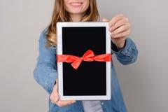 Vrouw die digitale tablet met rode die lintgift tonen op grijs van de technologiemensen van achtergrondstootkussenpda modern vrij royalty-vrije stock afbeeldingen