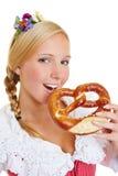 Vrouw die in dirndl een pretzel eten Stock Afbeeldingen