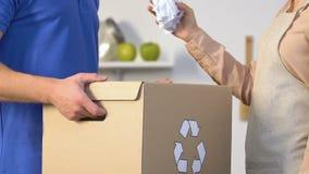 Vrouw die document werpen in het recycling van bak in mannelijke handen, afval het sorteren voor planeet stock videobeelden