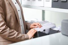 Vrouw die documenten van omslag in archief nemen stock afbeeldingen