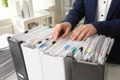 Vrouw die documenten van omslag in archief nemen stock foto