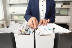 Vrouw die documenten van omslag in archief nemen royalty-vrije stock afbeelding