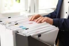 Vrouw die documenten van omslag in archief nemen stock afbeelding