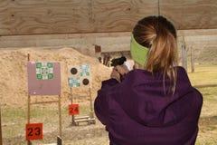Vrouw die doel schieten bij pistool die waaier schieten Stock Afbeeldingen