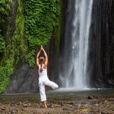 Vrouw die doend yoga tussen watervallen mediteren Royalty-vrije Stock Afbeeldingen