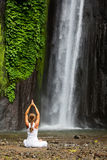Vrouw die doend yoga tussen watervallen mediteren Stock Afbeeldingen